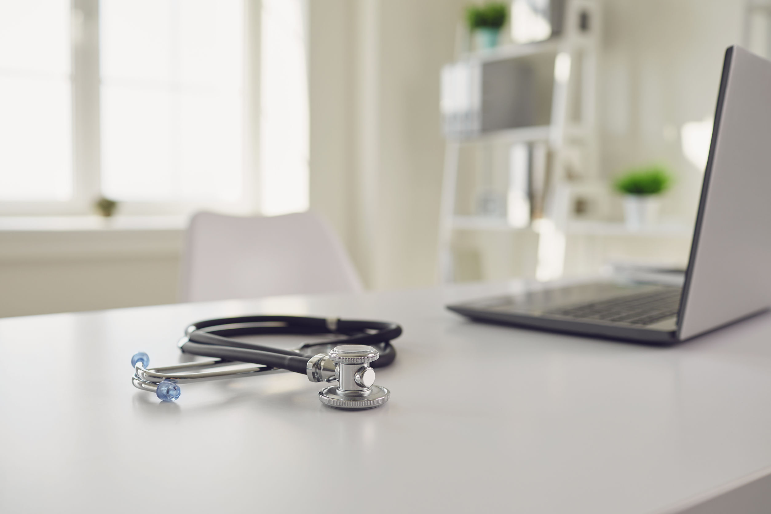 Doctor online. A stethoscope is on a white table with a laptop in blur at the hospital office. The concept of medical consultation for patients call to medical services. Consultation diagnosis remote sensing survey analysis of prescription medical insurance for sick people patients.